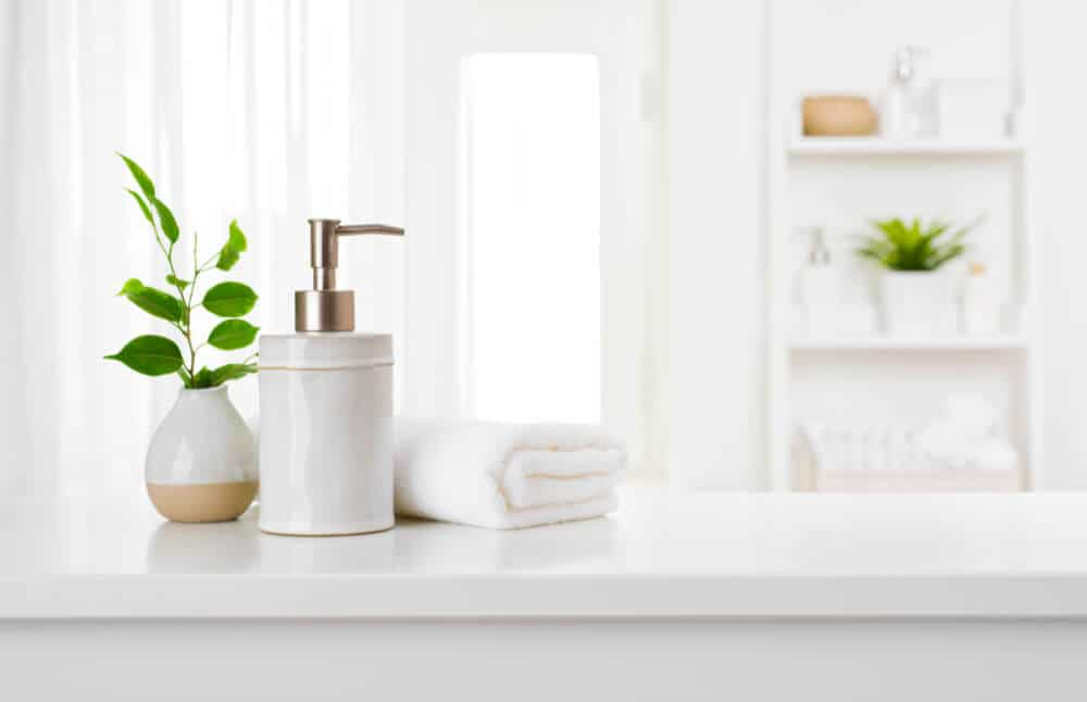 white and tan ceramic vase holding a stem of green leaves sitting next to white ceramic soap pump and a white folded towel with a view of bathroom shelves filled with a plant, white towels and body products blurred in the background.