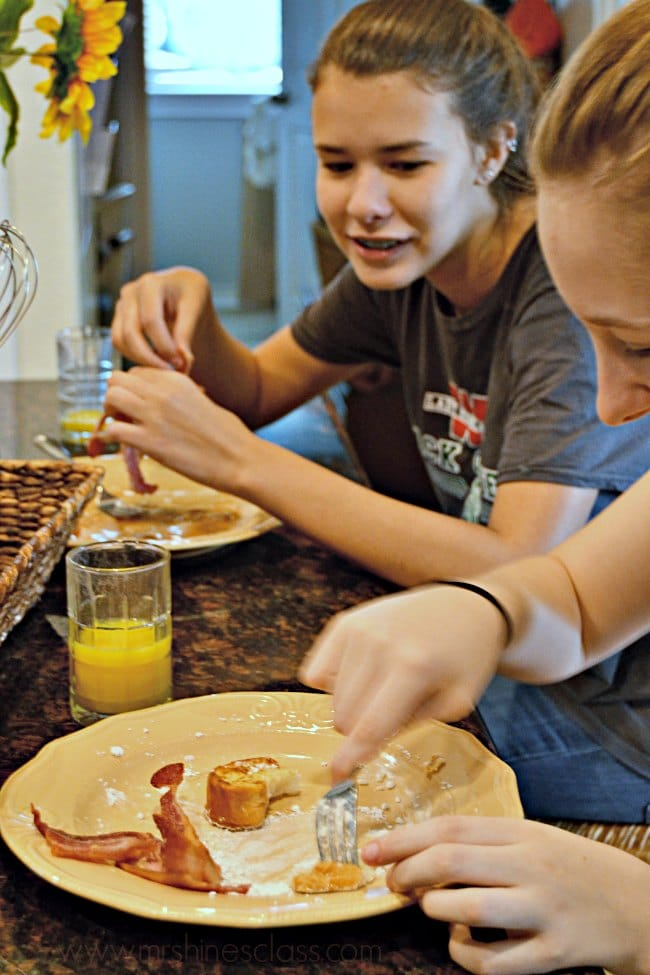 two teen girls eating french toast and bacon at a kitchen island