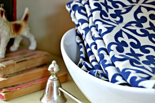 white and gold bowl with blue and white patterned cloth napkins sitting in it.