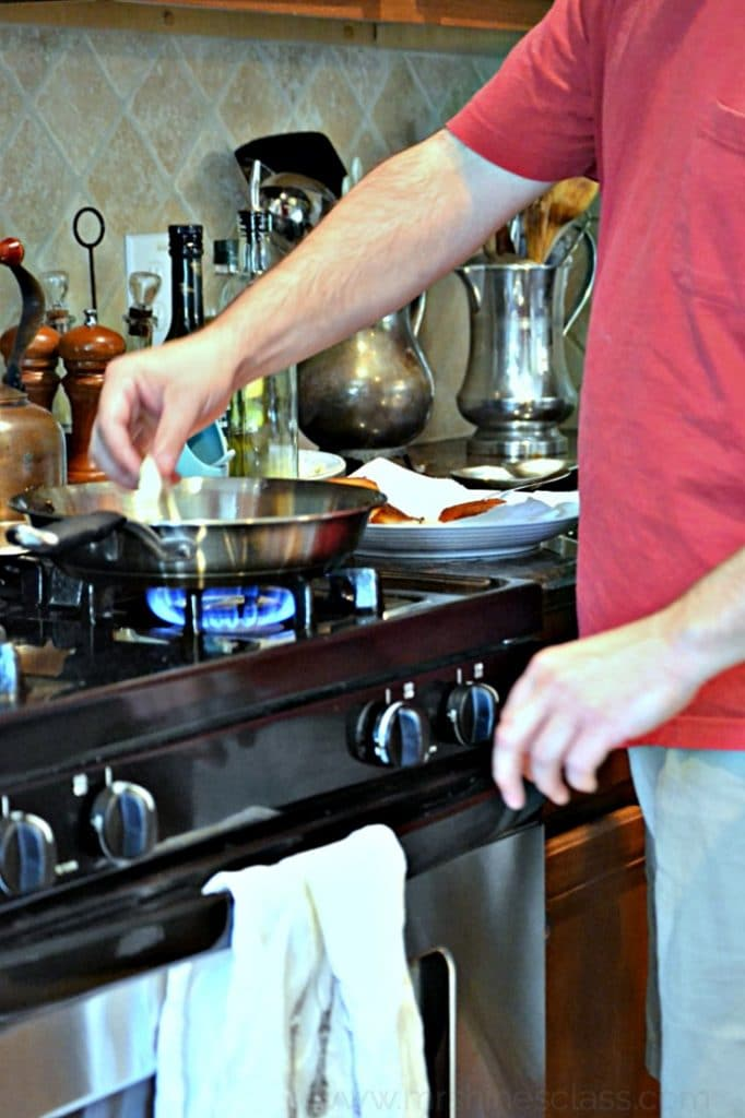 A man in a red shirt dropping a raw biscuit in a pan to fry.