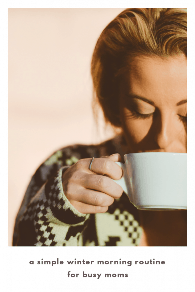 a woman wearing a cozy sweater sipping a drink