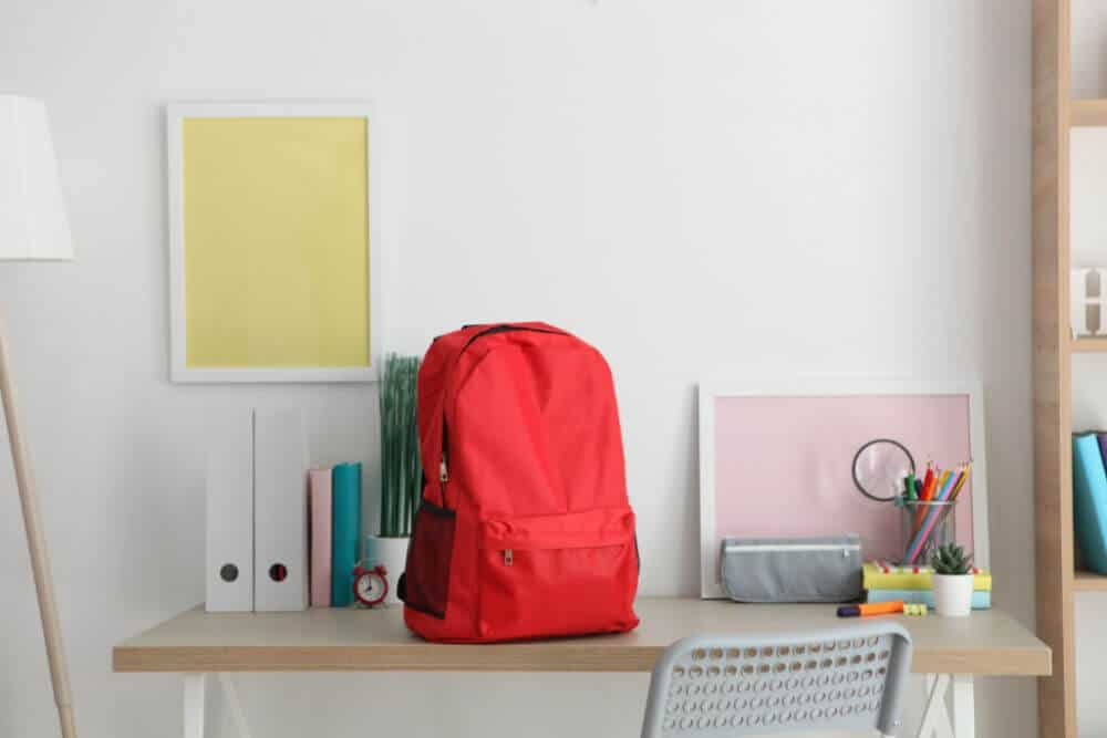red school backpack sitting on a light wood top desk. The desk has school supplies, a small red alarm clock, magazine file holders and a plant sitting on it.
