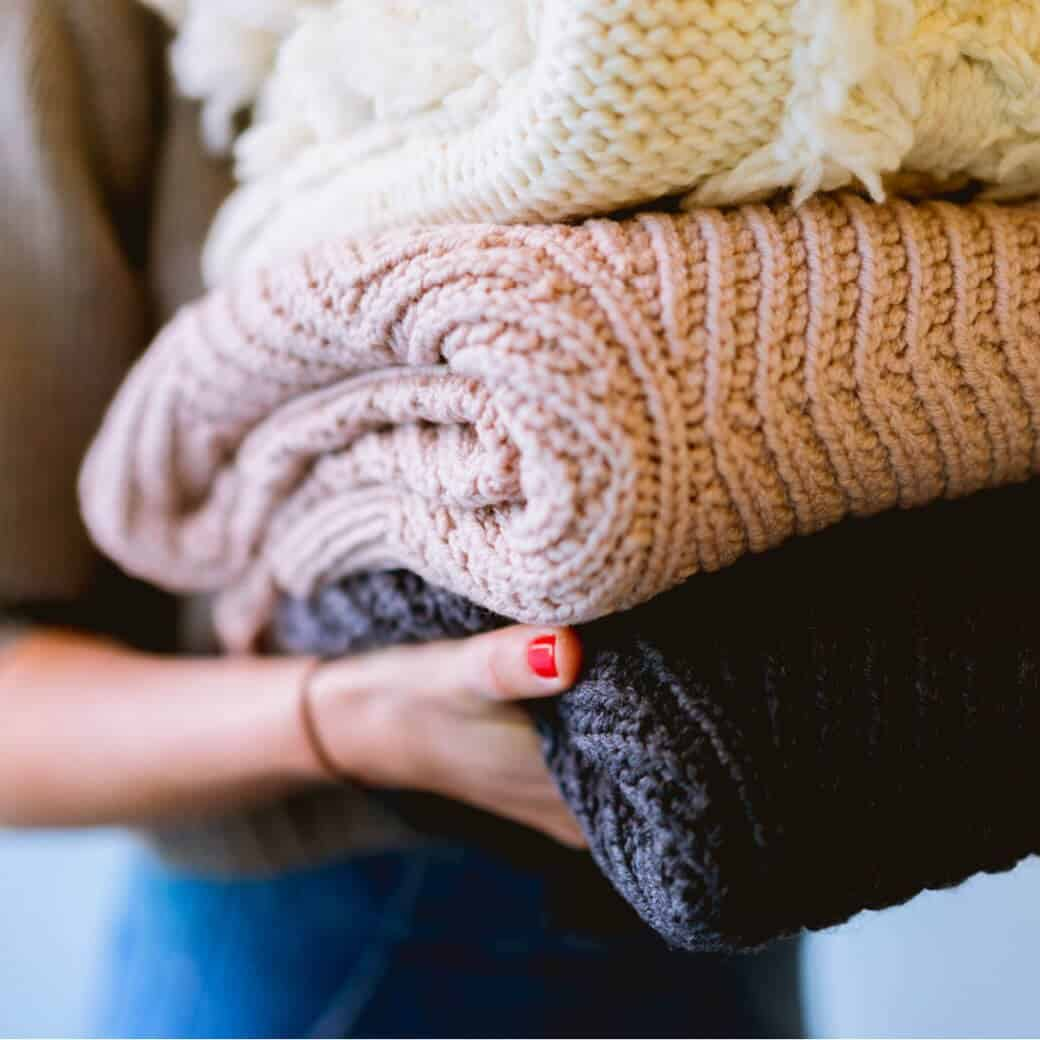 woman carrying folded knit blankets in a blog post about fall decluttering tips