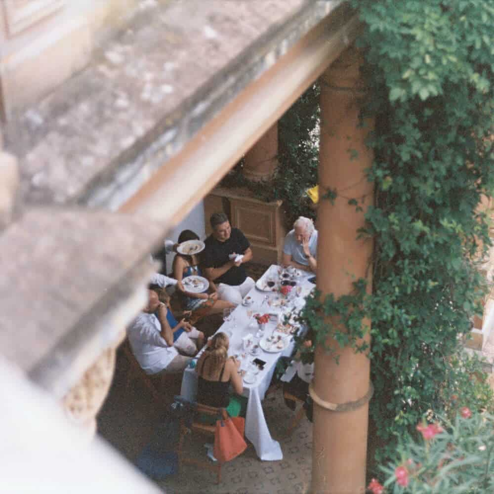 group of people eating a table outdoors under a patio