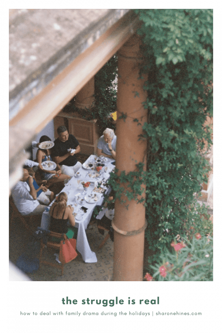 group of people eating outdoors around a rectangle table covered with a with a white tablecloth