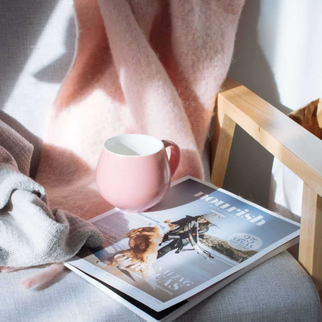 pink blanket and pink mug of coffee and magazine on a chair