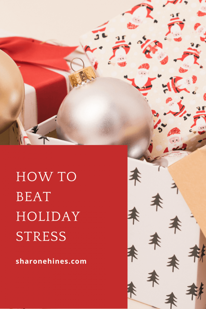 Gift boxes wrapped in Christmas wrapping paper and red ribbon  with shiny silver and gold ornaments sitting in the open gift boxes. Image says How to Beat Holiday Stress