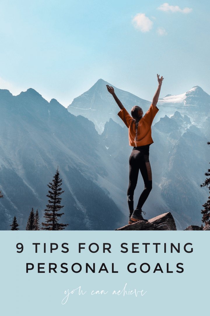 blonde woman with braided pony tail wearing an orange shirt and black leggings standing on top of a mountain with her arms raised up. Image says 9 Tips for Setting Personal Goals You Can Achieve