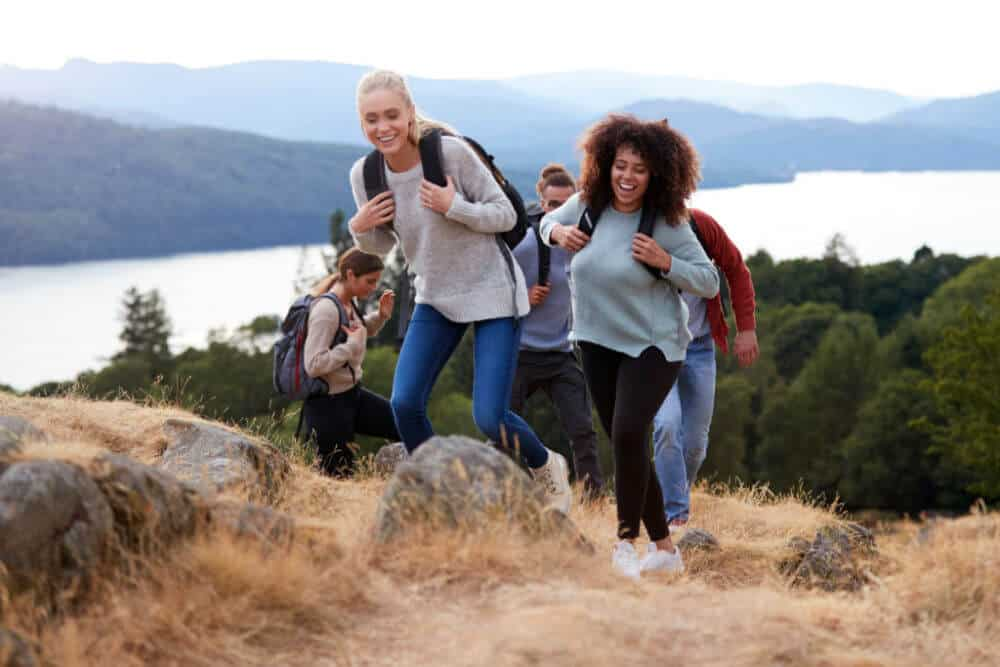 group of women wearing pants and sweaters and carrying backpack as they hike up a mountain.