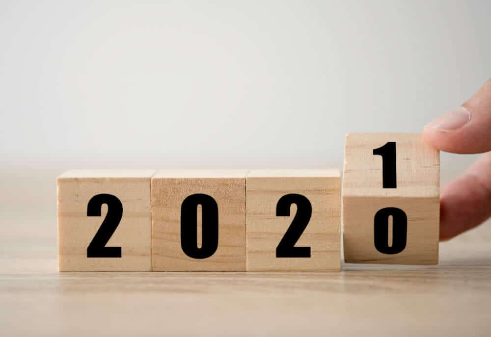 wooden blocks with the numbers 2020 with a person's hand turning the last zero over to 1.