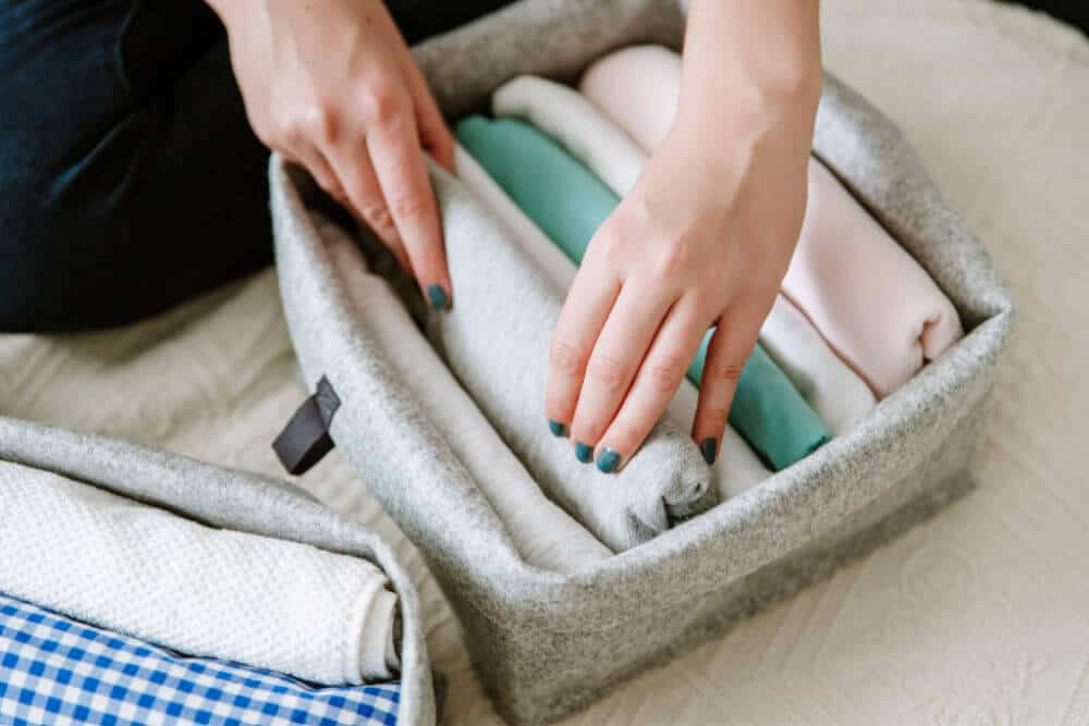 woman filing folded clothes in a gray cloth storage basket.