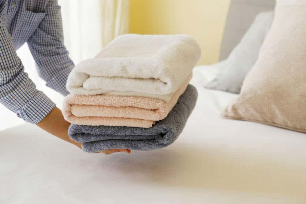 woman laying set of folded towels at foot of bed.