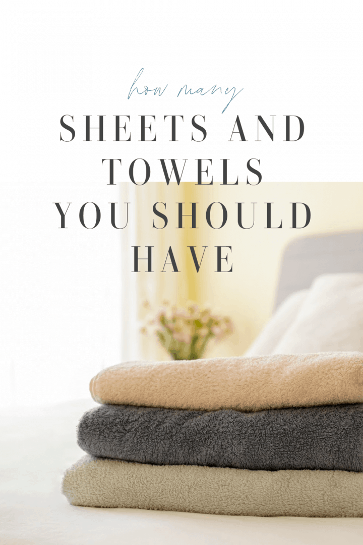 stack of folded towels sitting on the end of a bed with text that says How Many Sheets and Towels You Should Have