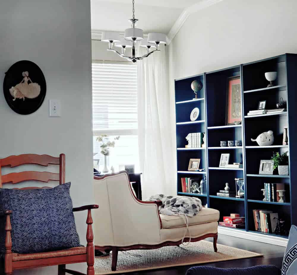 view of a cozy home office featuring an antique chaise lounge facing dark blue bookcases, white curtains and a chrome chandelier.