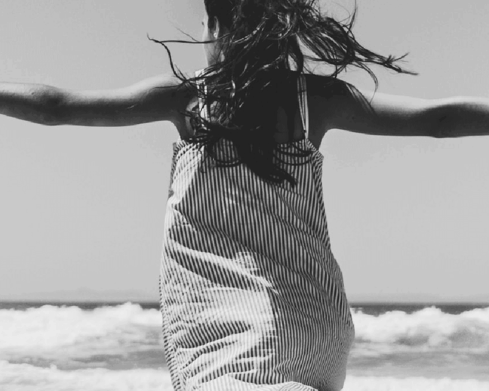 black and white photo of a woman wearing a striped cover up dress facing the ocean with her arms open wide.