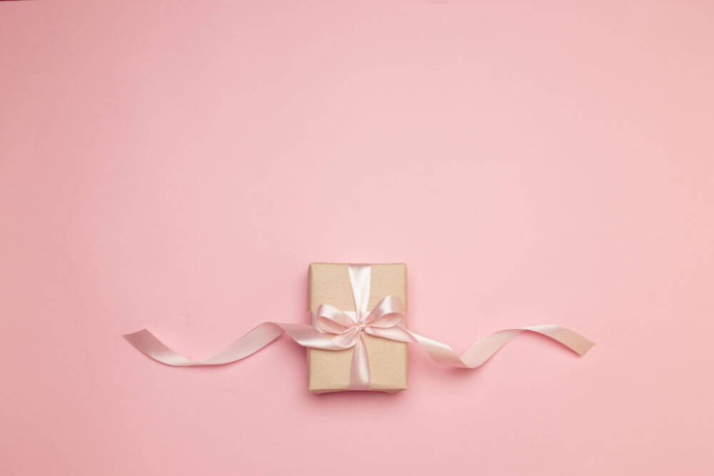 pink background with a small gift wrapped in brown butcher paper tied with a pink satin bow with long ribbons dangling off to each side.