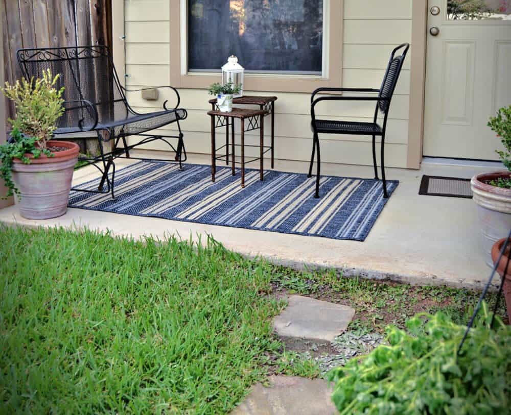 a back patio with black wrought iron glider and chair facing each other, anchored by a a blue, white and tan striped rug. Potted plants, and a white lantern accessorized the patio space.