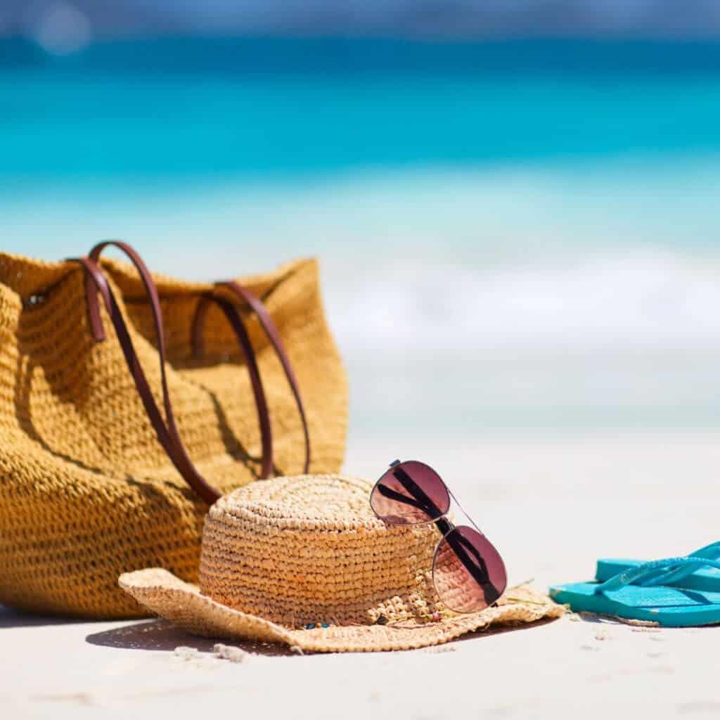 tan straw beach bag sitting on white beach sand next to light tan straw hat, aviator sunglasses and aqua blue flip flops