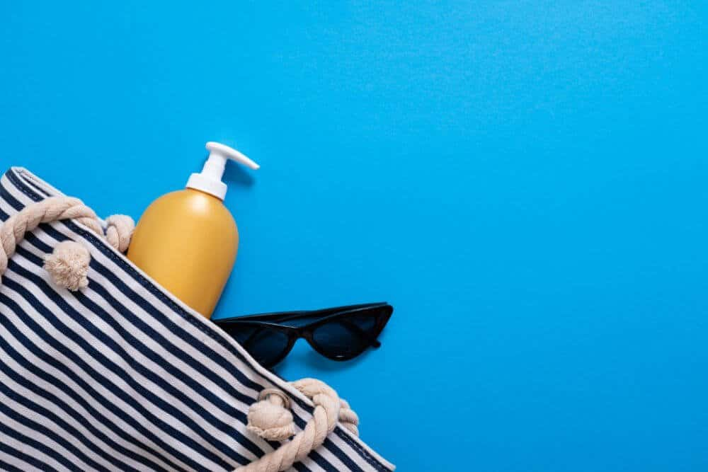 blue and white horizontal striped canvas beach bag with yellow bottle of sunscreen and a pair of black sunglasses spilling out. Laying on a sky blue background.