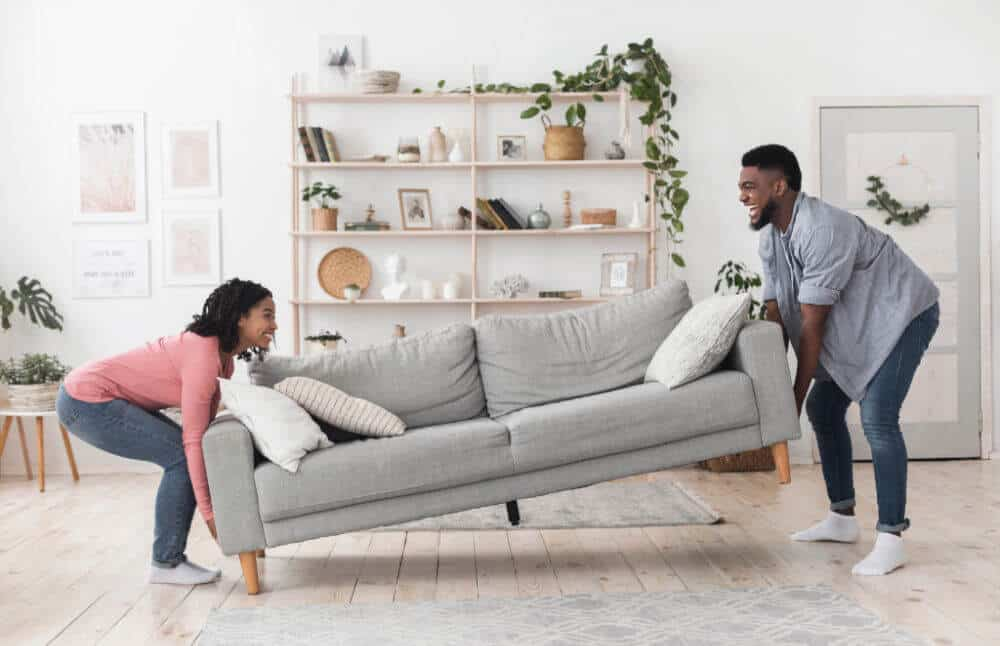 a smiling couple holding each end of a gray sofa putting the sofa in place on the floor.