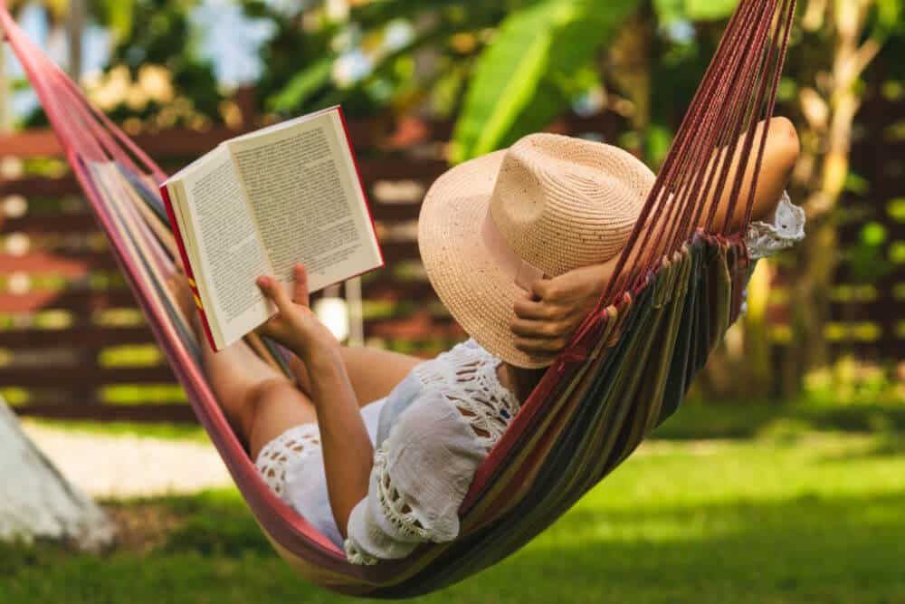woman in straw hat and white summer dress laying in striped hammock reading a book