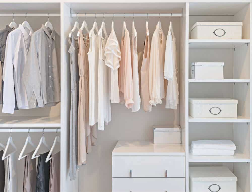 white and pastel colored clothes hanging in a white closet.