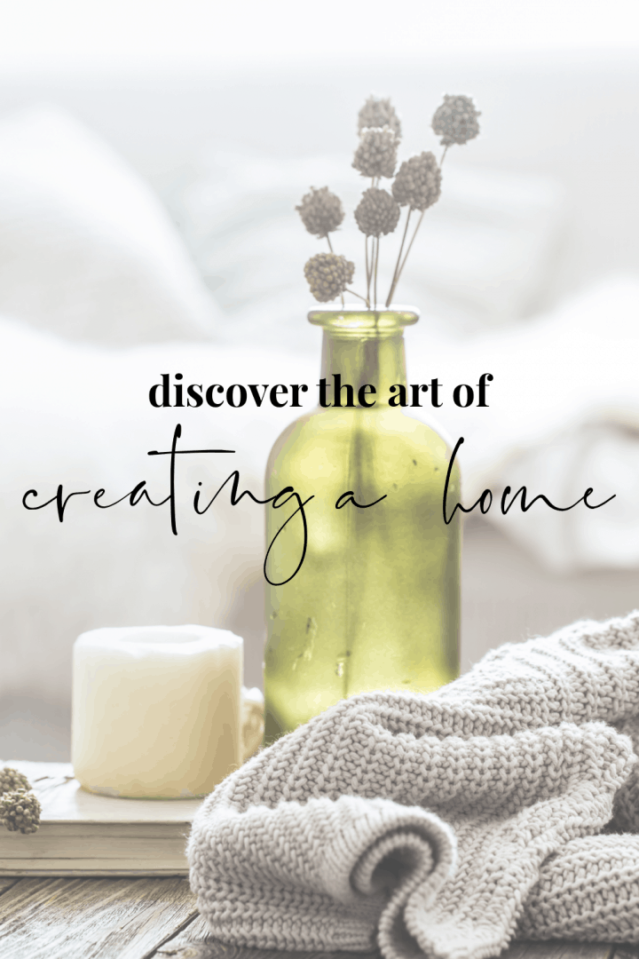 green glass vase holding flowers, sitting on a table next to a book, candle and chunky knit blanket. Text on image says discover the art of creating a home.