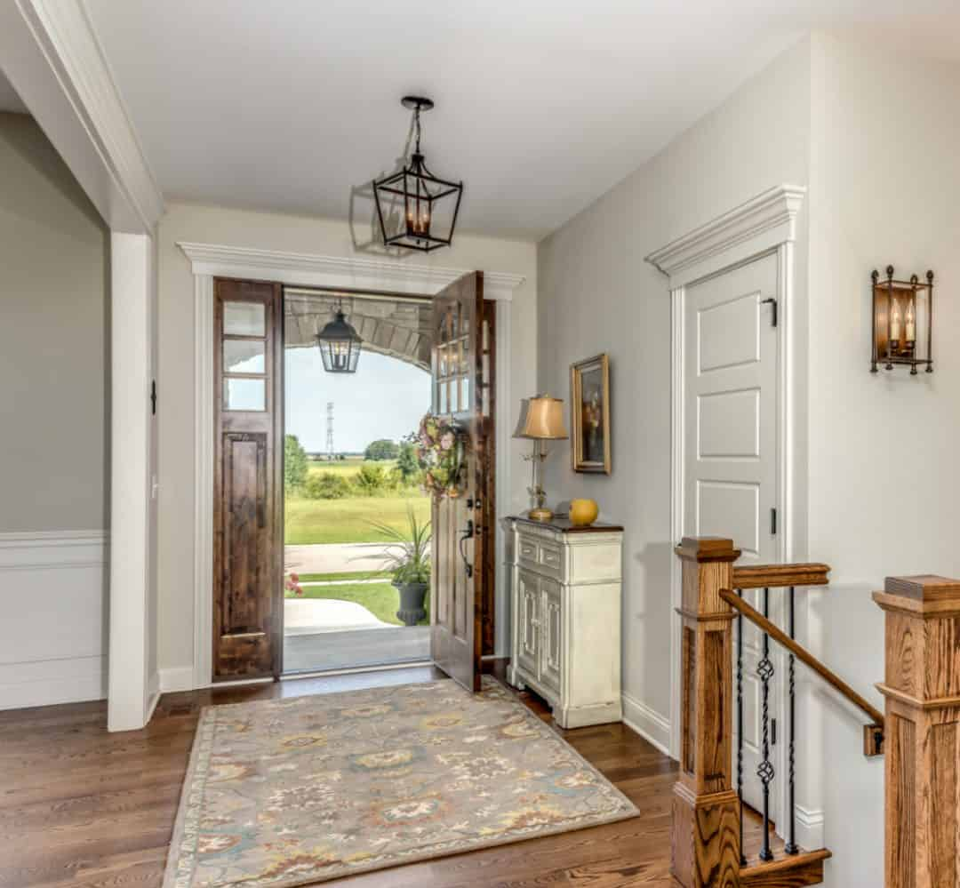A wood front door opening into a foyer with a small console table holding a lamp and small decor.