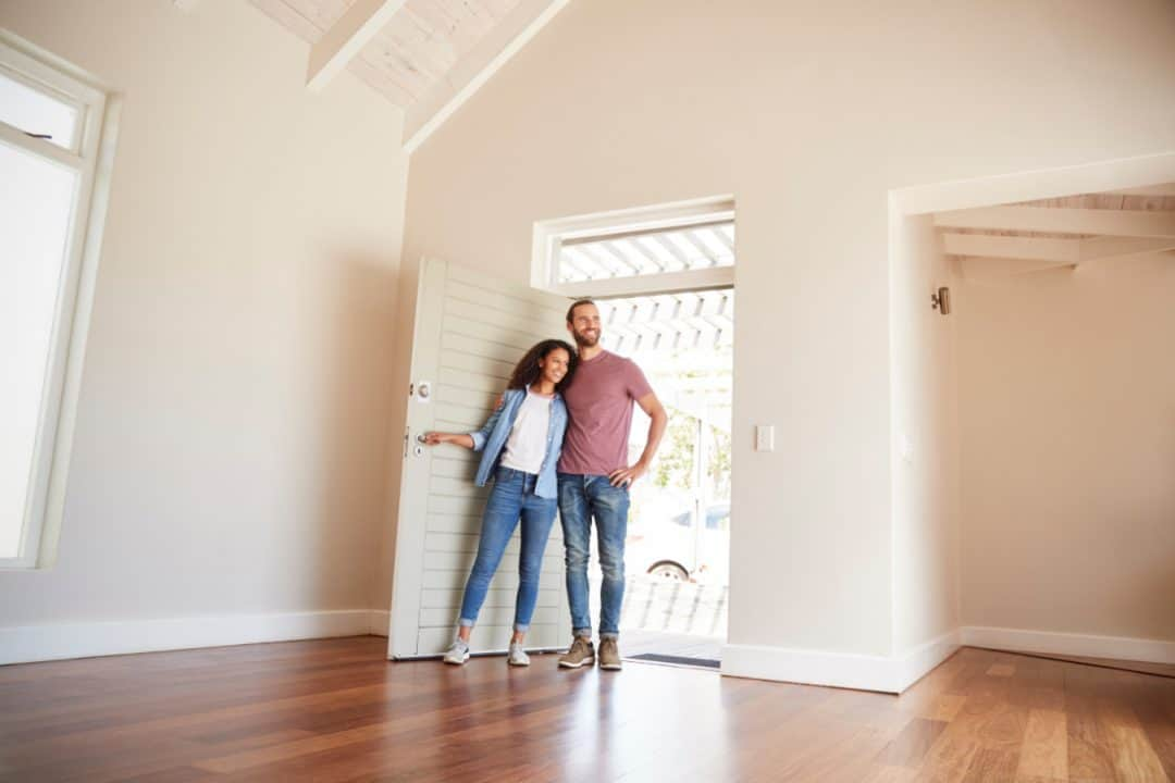 a couple standing in the doorway to a large entryway that opens into the living room.