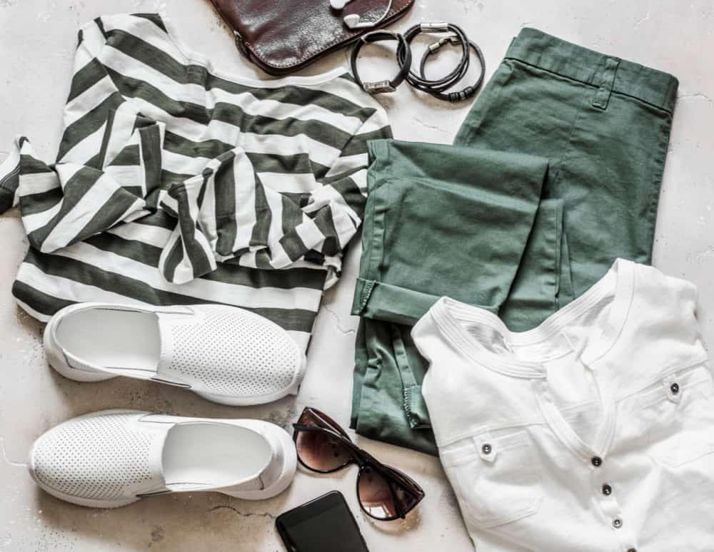 Spring summer set of women's casual wear - cotton pants, white t-shirt, striped pullover, leather sneakers, bag, smartphone and accessories on a light background, top view.   Post on How to Store Seasonal Clothes