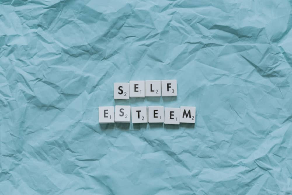 light blue wrinkled paper background with scrabble tiles on it that say self esteem. the image is in post on how to overcome low self-esteem