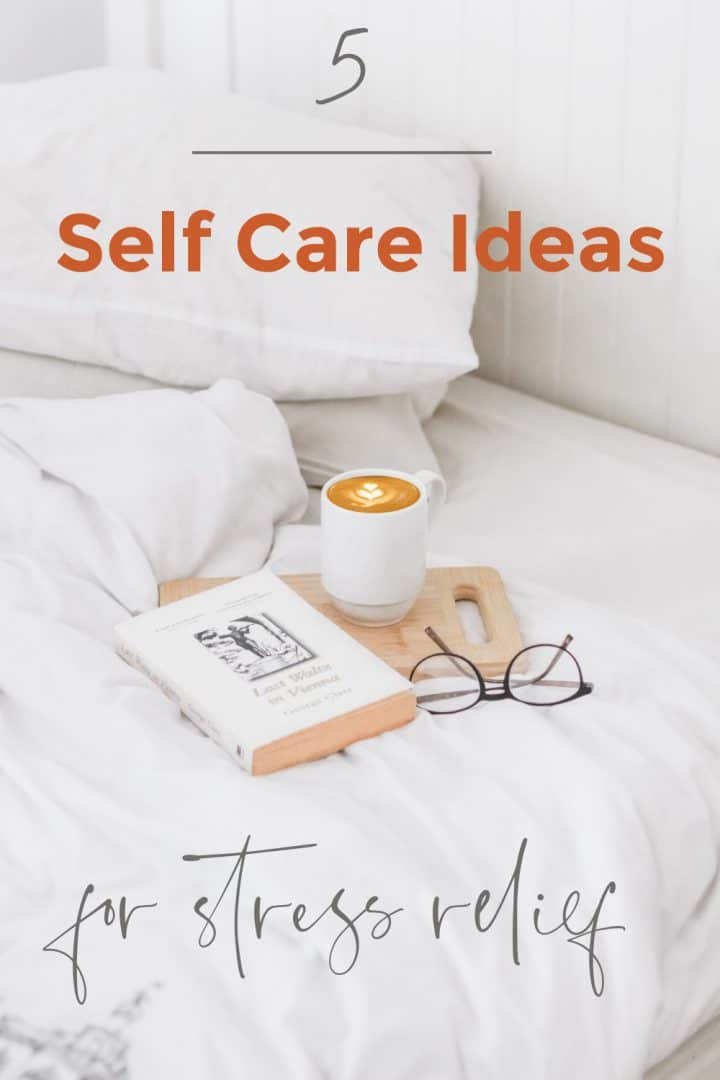 white sheets rumpled on a bed with two white pillows stacked on top of each other. a cup of coffee in a white mug sitting on a wooden cutting board near a book and some reading glasses. Text reads 5 Self Care Ideas for Stress Relief.